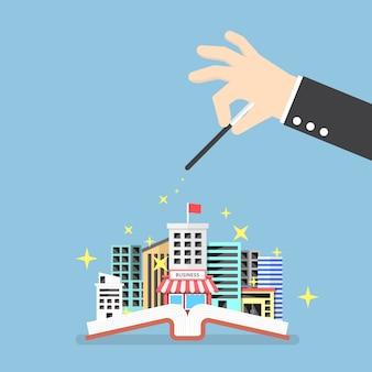 Mano de hombre de negocios usar mágico para construir ciudad a partir de libro abierto