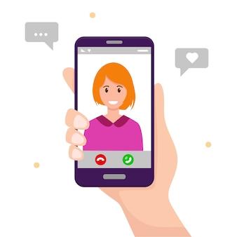 Mano humana con smartphone con mujer joven en pantalla