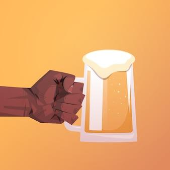 Mano humana sosteniendo una jarra de cerveza plana concepto de celebración de fiestas octoberfest