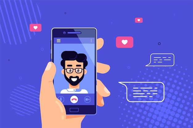 Mano humana sosteniendo smartphone con personaje masculino en pantalla. videollamada, video chat en línea, tecnología de internet.