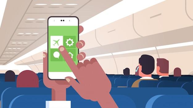 Mano humana sosteniendo el teléfono inteligente con las reglas del modo de vuelo del avión concepto de seguridad moderna placa de avión con pasajeros plana horizontal
