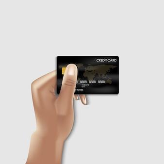 Mano humana sostiene tarjeta de crédito para pago de compras.
