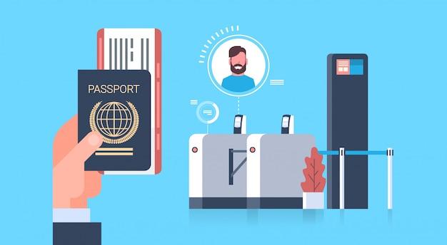 Mano de negocios que sostiene el pasaporte y los boletos al avión sobre el escáner en el aeropuerto hombre durante el registro para el concepto de salida
