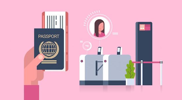 Mano de negocios que sostiene el pasaporte y los boletos al avión sobre el escáner en el aeropuerto mujer en el registro para el concepto de salida