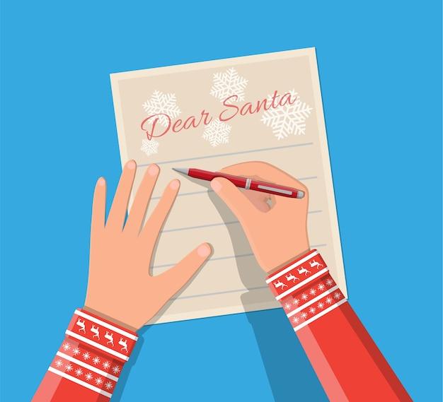 Mano de niño con pluma escribiendo carta a santa claus. lista de deseos de vacaciones. navidad víspera de año nuevo vacaciones de navidad.