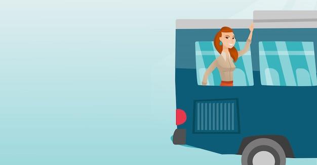 Mano que agita de la mujer caucásica joven de la ventana del autobús.