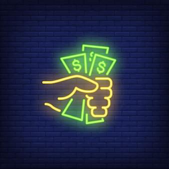 Mano que lleva a cabo billetes de dólar signo de neón