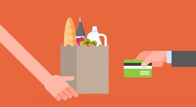 Mano que paga por la bolsa de papel llena de productos comestibles con tarjeta de crédito, pedido de comida en línea y concepto de servicio de entrega