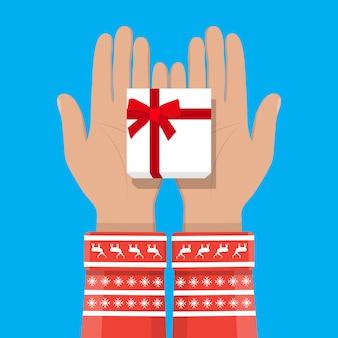 Mano que sostiene la caja de regalo blanca con lazo rojo
