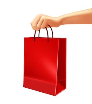 Mano que sostiene el ejemplo rojo del bolso de compras