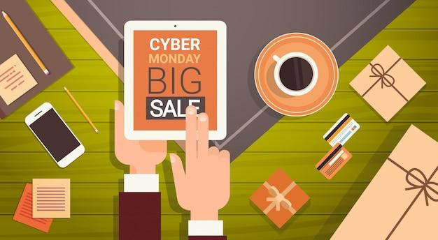 Mano que sostiene la tableta digital con el mensaje de cyber monday big sale, banner de compras en línea