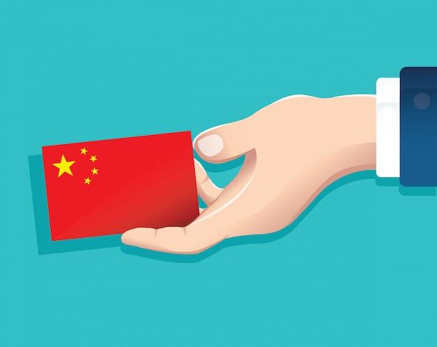 Mano que sostiene la tarjeta de la bandera de china