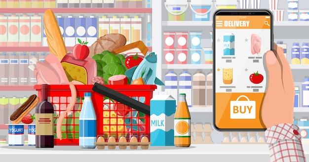 Mano que sostiene el teléfono inteligente con la aplicación de compras. entrega en tienda de abarrotes. pedido por internet. supermercado online. cesta de la compra con comida y bebida. leche, verduras, carne, queso. ilustración vectorial plana