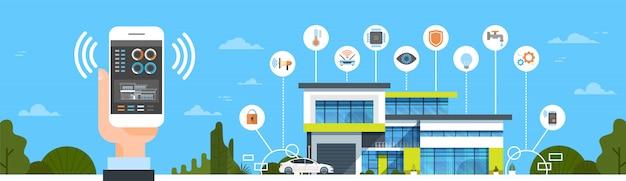 Mano que sostiene el teléfono inteligente con la interfaz de control del sistema del hogar inteligente modern house house automation concept hor
