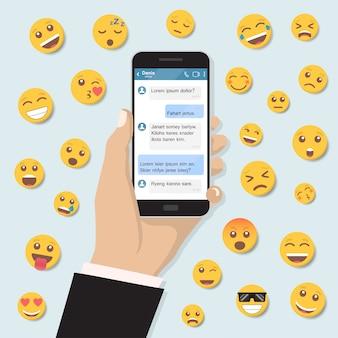 Mano que sostiene el teléfono inteligente con mensajería de chat y emoticon en un diseño plano
