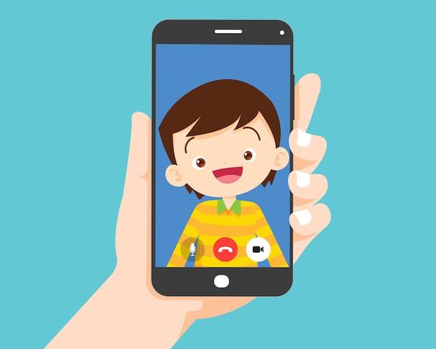 Mano que sostiene el teléfono inteligente con el niño de los niños en la pantalla. videollamada con el estudiante.