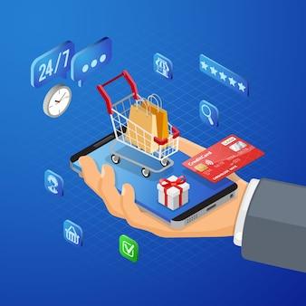 Mano con smartphone, carrito de compras, tarjeta de crédito. compras en internet y concepto de pagos electrónicos en línea. iconos isométricos.