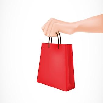 Mano sosteniendo la bolsa de papel rojo