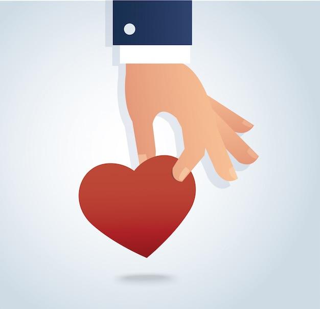 Mano sosteniendo el corazón rojo