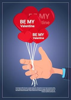 Mano sosteniendo globos de aire con be my valentine banner de texto con espacio de copia
