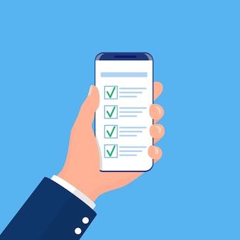 La mano sostiene el teléfono inteligente con lista de verificación completa con marcas de verificación.