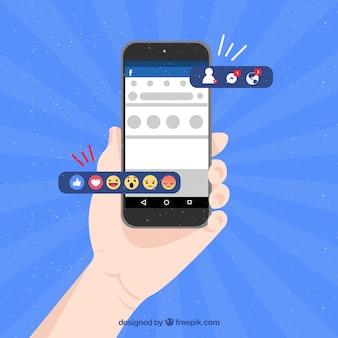 Mano sujetando móvil con notificaciones de facebook