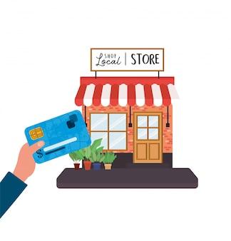 Mano sujetando la tarjeta de crédito frente al diseño de la tienda local de la tienda minorista, compra y tema del mercado