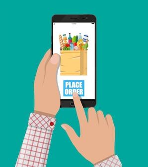 Mano y teléfono inteligente con bolsa de compras
