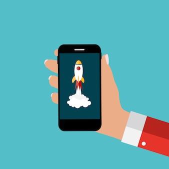 Mano con teléfono móvil abstracto y cohete como puesta en marcha. modelo