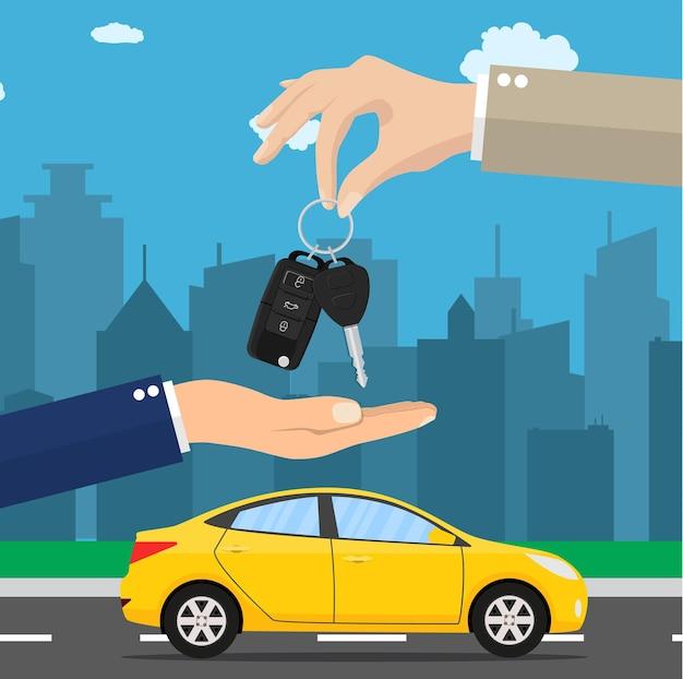 Mano del vendedor de coches dando la llave al comprador. alquiler de coches