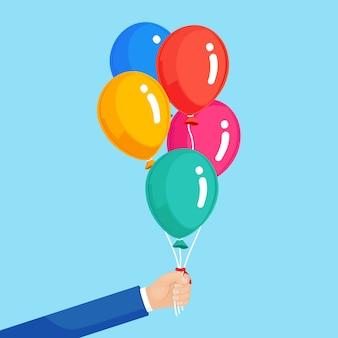 Manojo de globo de helio en mano, bolas de aire voladoras