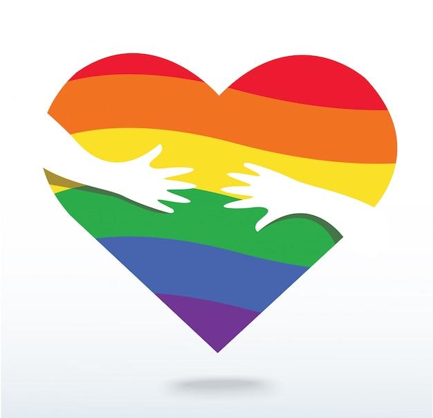 Manos abrazando el corazón de la bandera del arcoiris