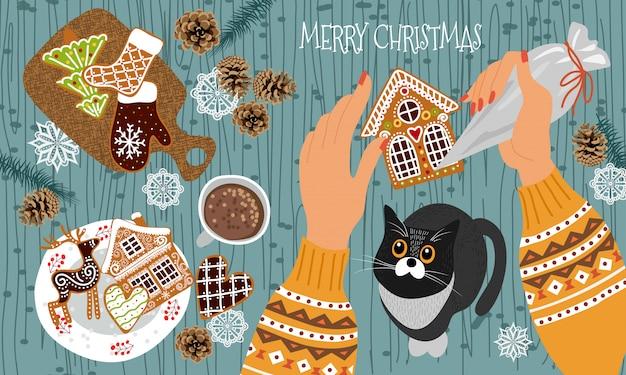 - las manos con una bolsa de repostería decoran las galletas de jengibre con glaseado y el gato observa el proceso