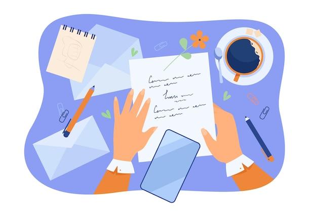 Manos de carácter escribiendo carta en el escritorio con papeles, lápiz, sobres y taza de café.