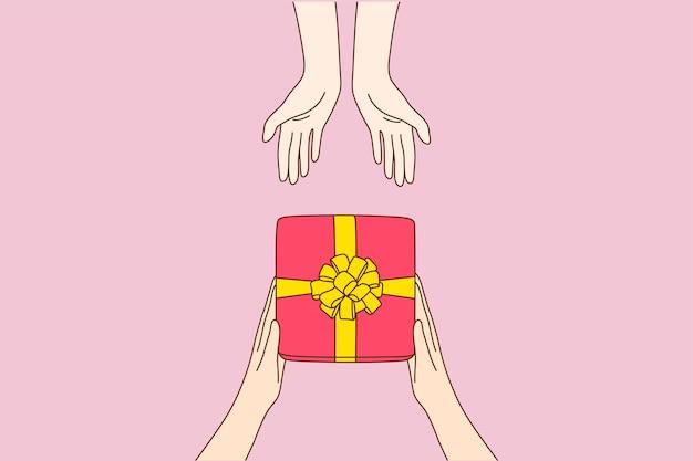 Manos de dibujos animados de hombre dando caja roja presente con cinta dorada en brazos de mujer