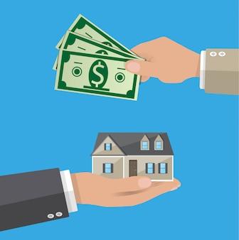 Manos con dinero y casa. bienes raíces