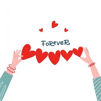 Manos femeninas que llevan a cabo la forma de papel de la fila del corazón para saludar el concepto.