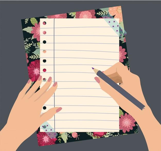 Las manos femeninas sostienen un lápiz con las flores hermosas libreta