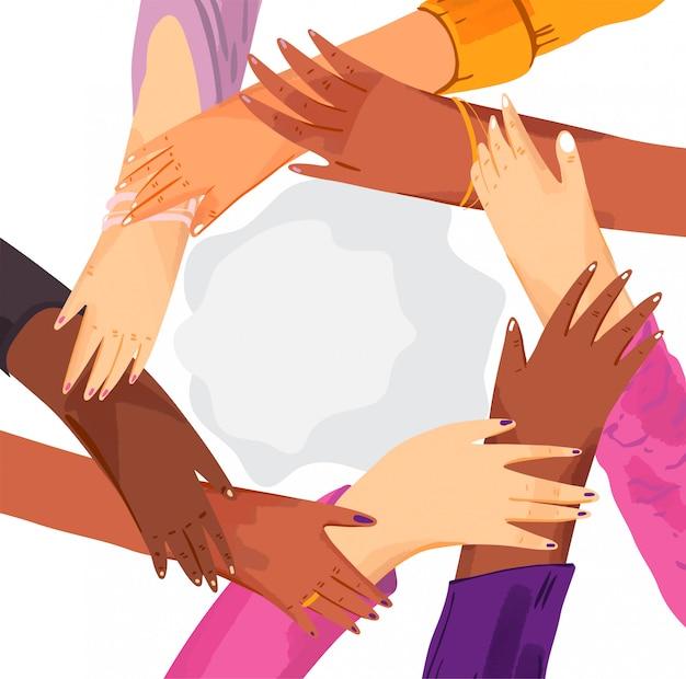 Manos de un grupo diverso de mujeres juntando en círculo.