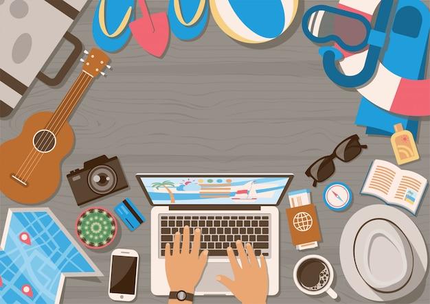 Manos del hombre planeando viaje en la computadora portátil con elementos de vacaciones de verano en la mesa de madera desde la vista superior en estilo plano