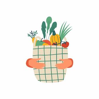 Las manos humanas sostienen la cesta ecológica llena de verduras aisladas en blanco