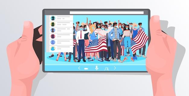 Manos humanas usando tablet pc viendo videos en línea personas con máscaras sosteniendo banderas de estados unidos celebración del día del trabajo coronavirus concepto de cuarentena retrato