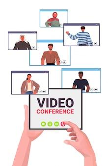 Manos humanas utilizando tablet pc chateando con colegas de raza mixta durante la llamada de video conferencia en línea reunión comunicación concepto vertical ilustración