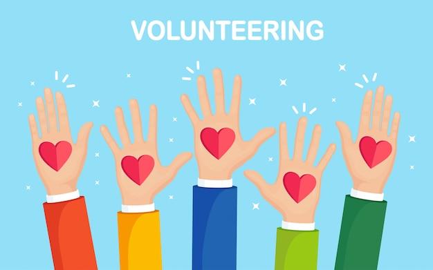 Manos levantadas con corazón rojo. voluntariado, caridad, donar sangre concepto. gracias por el cuidado. voto de multitud.
