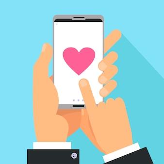 Manos masculinas que sostienen el teléfono con gran corazón en la pantalla
