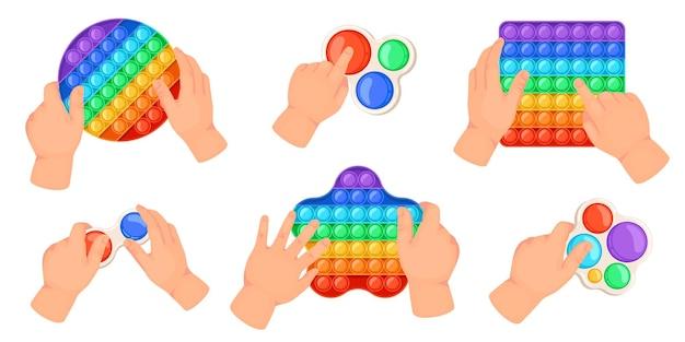 Las manos de los niños sostienen pop, jugando con juguetes inquietos. niños haciendo estallar burbujas de juegos sensoriales. antiestrés, simple, hoyuelo, arco iris, juguetes, vector, conjunto, de, diferente, formas, como, redondo, cuadrado, y, estrella