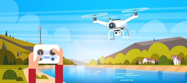Manos que sostienen el mando a distancia para un moderno vuelo de drone sobre un hermoso color natural