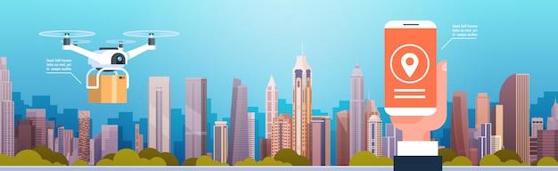 Manos que sostienen el teléfono inteligente con el ícono de destino para la moderna tecnología de entrega de drones en los edificios de la ciudad