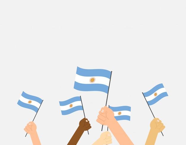 Manos sosteniendo banderas argentinas