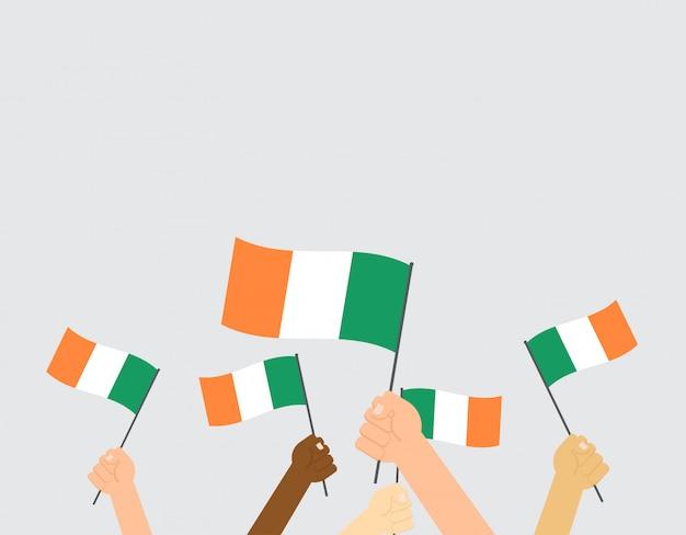 Manos sosteniendo banderas de irlanda